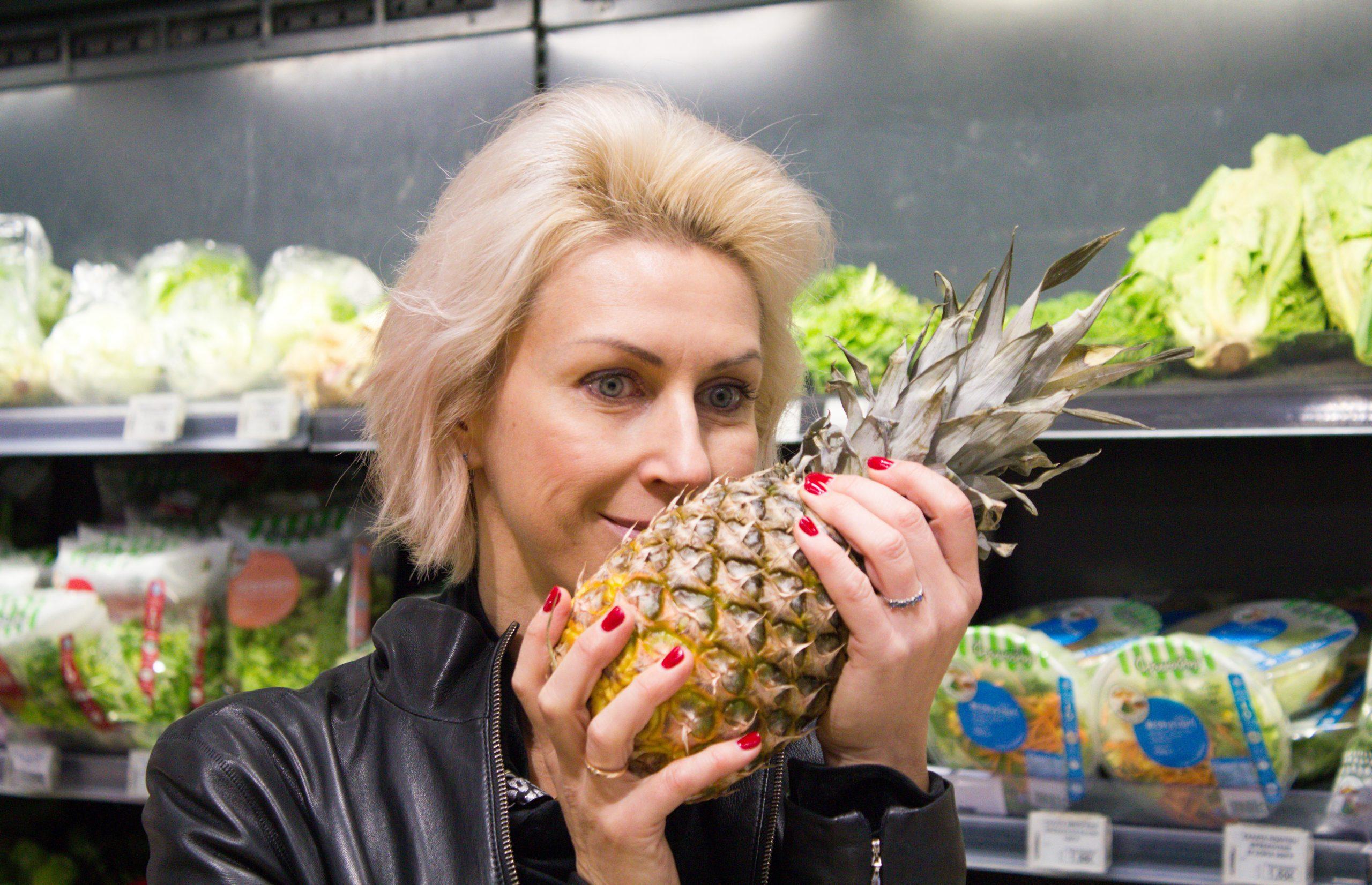 Девушка держит в руках ананас